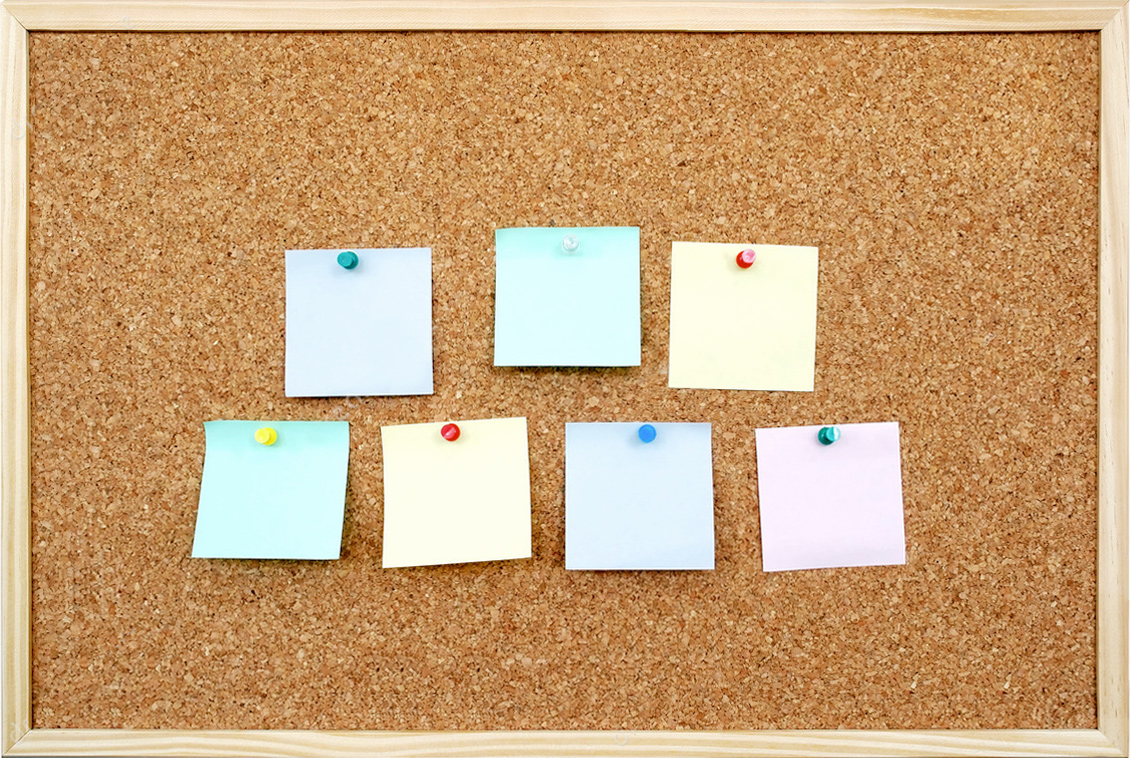Image of a cork board with post-it notes attached.