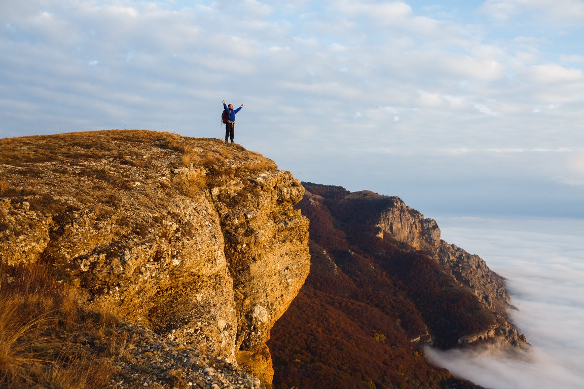 Image of someone standing at the top of a hill, victorious for New Month, New You Posts