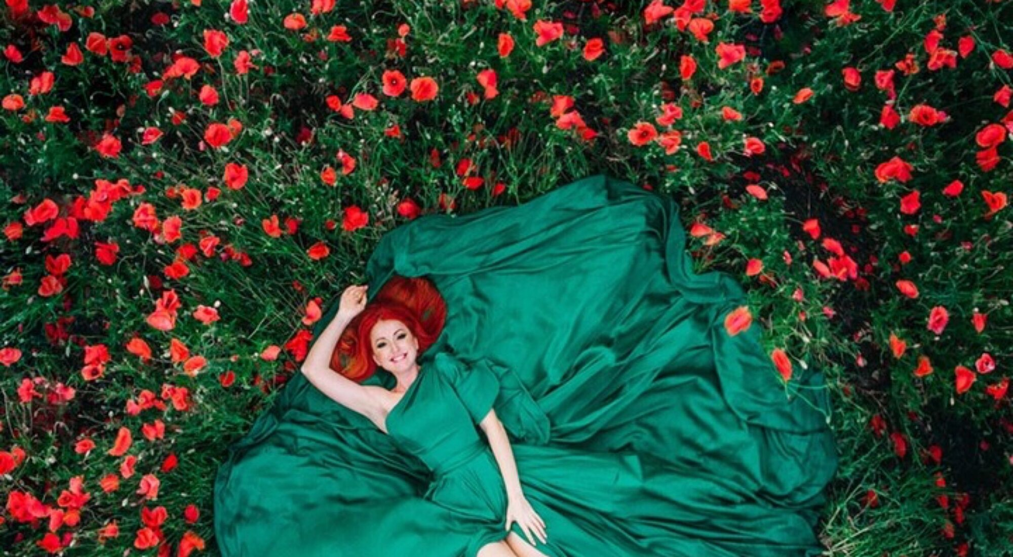 Image of a lady in a green dress laying down in the grass.